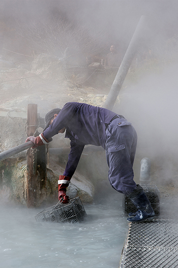 photo of man bending over steamy water