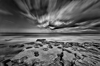 Black and white image of clouds, rocks and water by Lewis Kemper